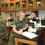 A military school student in biology class takes notes.