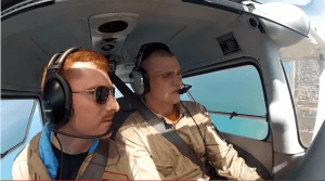 An instructor and student pilot perform a turn above the South-Texas shore line.