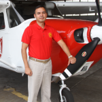 Mr. Mitri Garib standing beside a Redhawk 172 flight training aircraft.
